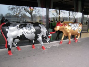 Two life-sized cow statues facing each other. One has traditional cow markings but in silver with black spots. The one on the right is gold with white wings painted on its body and a huge white flower painted on its back hip. Both cows have red tails and hooves as well as red masks over their eyes.